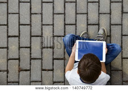 Boy with tablet outdoors. Child with pc computer sitting on the pavement. Top view. Technology computer addiction education concept