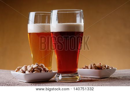 Glasses of beer and pistachio nuts in a white dishes