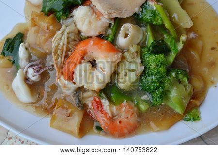 stir-fried large noodle with seafood in gravy sauce on dish