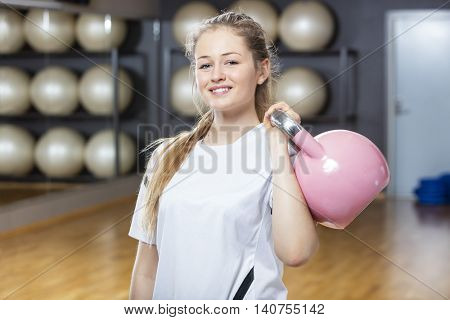 Attractive Woman Lifting Kettlebell In Gym