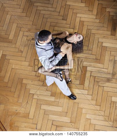 Sensuous Woman And Man Performing Tango On Hardwood Floor