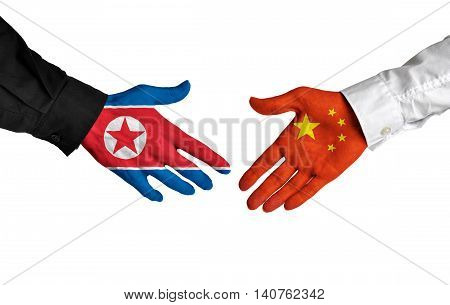 North Korea and China leaders shaking hands on a deal agreement