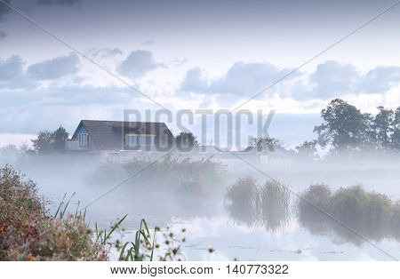 farmhouse by river n morning mist netherlands