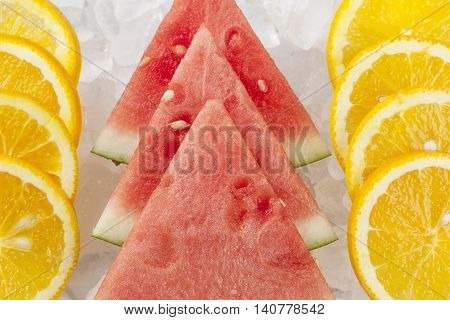 Close up of orange and watermelon slices. Rows of orange slices and watermelon wedges stacked up on ice.
