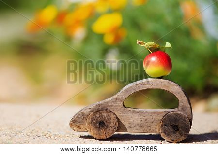 harvesting. wooden toy car with an apple. ripe apple on the car roof. the concept of farmers' delivery of fruits and vegetables. empty space for your text