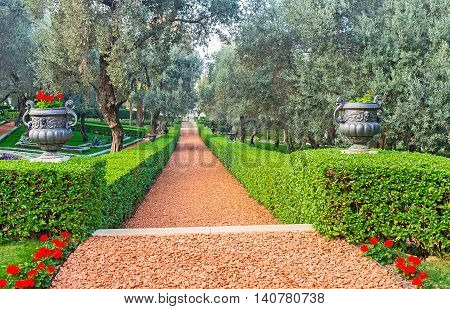 The red footpath in Bahai Garden surrounded by trimmed bushes and vases with flowers Haifa Israel.