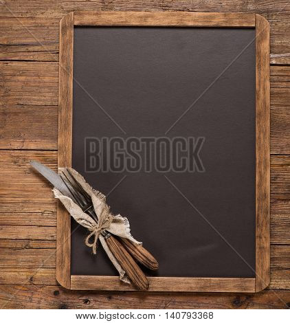 View from above of vintage spoon and fork tied with string on linen napkin on a blackboard on a rustic wooden table with copy space.