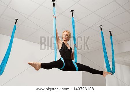 Young beautiful blonde girl smiling, looking at camera, practicing aerial yoga in gym.