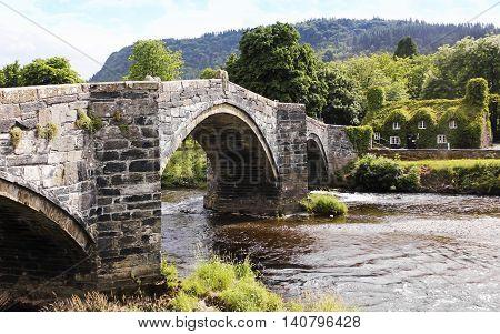 LLANRWST, WALES, JUNE 27. Pont Fawr Bridge and Tu Hwnt I'r Bont Tearoom on June 27, 2016, in Llanrwst, Wales. A View of Pont Fawr Bridge and Tu Hwnt I'r Bont Tearoom in Llanrwst Wales.