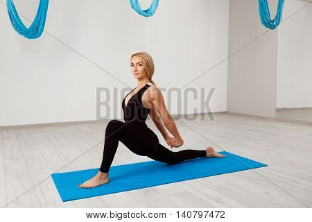 Young beautiful sportive blonde girl smiling, looking at camera, practicing yoga in gym.