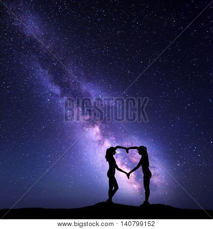 Girls Holding Hands In Heart Shape. Landscape With Milky Way