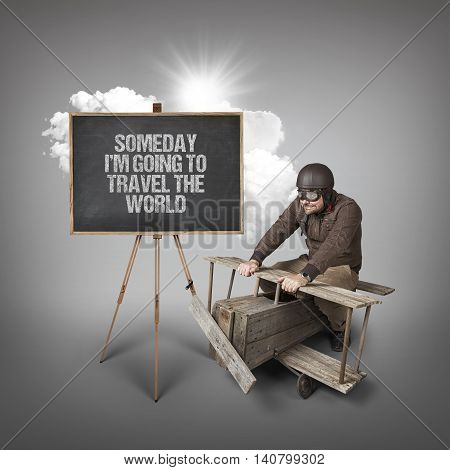 Someday Im going to travel the world text on blackboard with businessman and wooden aeroplane