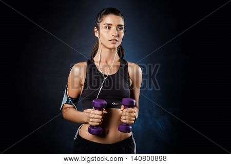 Young beautiful bruntete sportive girl training with dumbbells over dark background. Copy space.