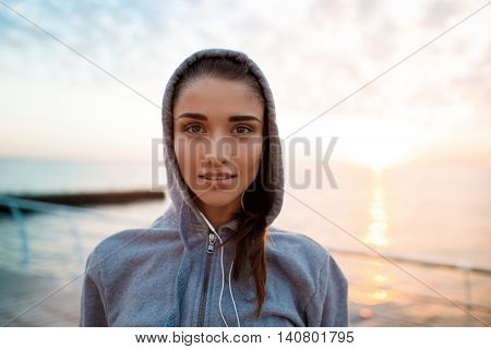 Portrait of young beautiful brunette sportive girl at sunrise over seaside. Copy space.