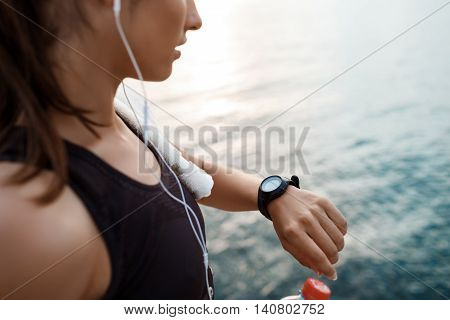 Young beautiful brunette sportive girl looking at watch at sunrise over seaside. Copy space.