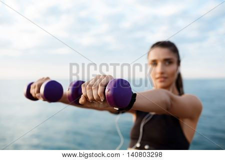 Young beautiful brunette sportive girl training at sunrise over seaside. Copy space.