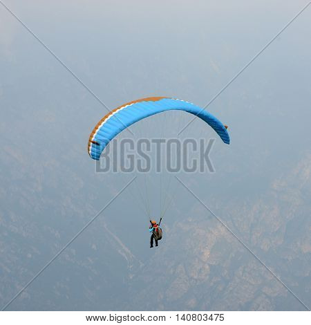 Paraglider flying over mountains at Lake Garda (Italy)