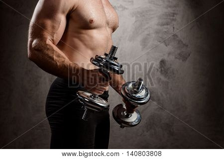 Close up photo of powerful sportsman training with dumbbells over dark background. Copy space.