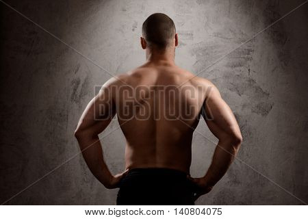 Close up photo of sportive man's body standing back to camera over dark background.