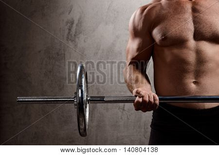 Close up photo of young powerful sportsman training with barbell over dark background. Copy space.