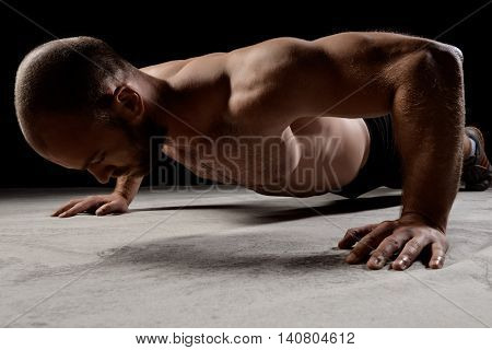 Young powerful sportsman training push ups on floor over dark background.