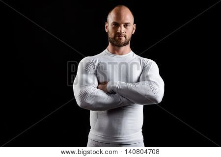 Young powerful sportsman in white clothing looking at camera, smiling, arms crossed over black background.