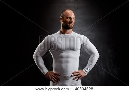 Young powerful sportsman in white clothing smiling over black background. Copy space.