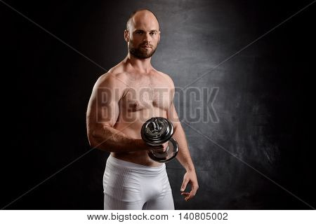 Young powerful sportsman training with dumbbells, looking at camera over black background. Copy space.
