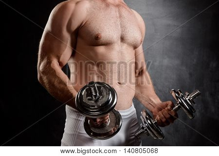 Close up photo of young powerful sportsman training with dumbbells over black background.