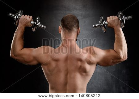 Young powerful sportsman training with dumbbells, standing back to camera over black background.