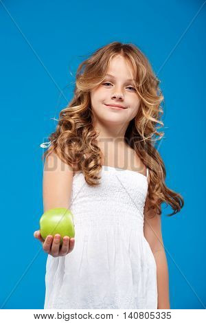 Young pretty girl holding green apple, looking at camera, smiling over blue background.