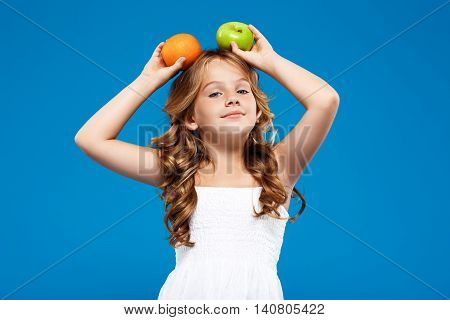 Young pretty girl holding apple and orange above head, smiling, looking at camera over blue background. Copy space.