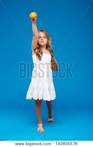 Young pretty girl holding oranges, looking at camera over blue background. Copy space.