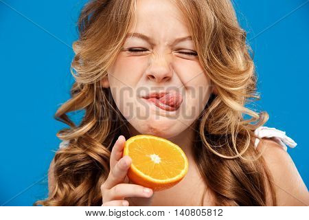Young pretty girl holding orange, showing tongue, eyes closed over blue background. Copy space. Close up.