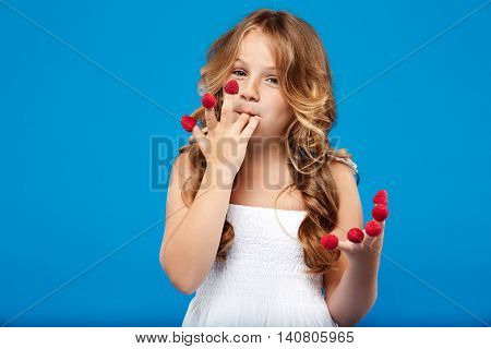 Young pretty girl eating raspberry, looking at camera over blue background. Copy space.