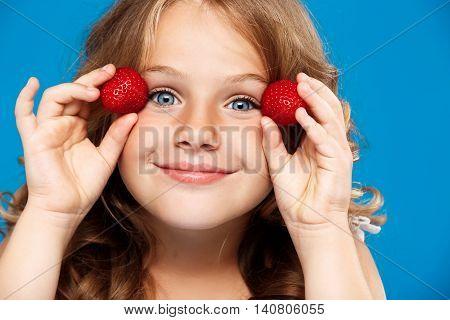 Young pretty girl holding strawberry, smiling, looking at camera over blue background.