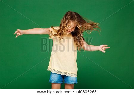 Young pretty girl dancing, smiling over green background. Copy space.