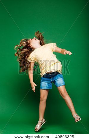 Young pretty girl jumping, looking up over green background.