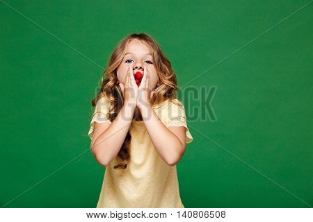 Young pretty girl eating raspberry, looking at camera over green background. Copy space.