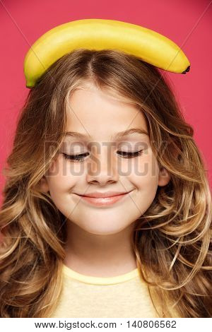 Young pretty girl holding banana on head, smiling over pink background.