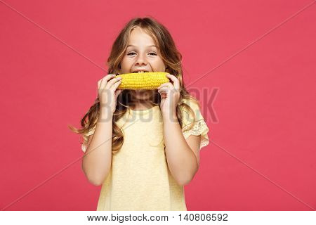 Young pretty girl eating corn, looking at camera over pink background. Copy space.