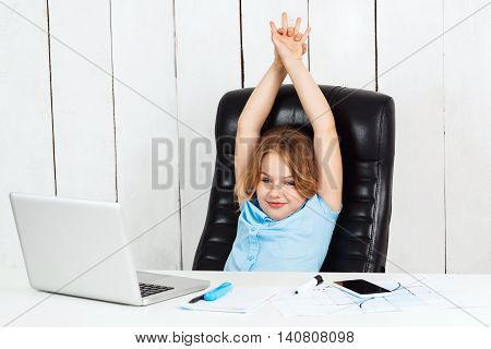 Young beautiful girl sitting at working place, smiling, hands above head, in office.