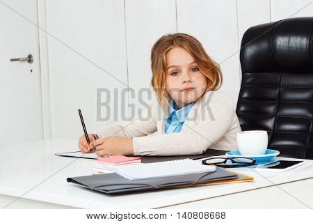 Young beautiful girl sitting at working place, writing, looking to camera in office.