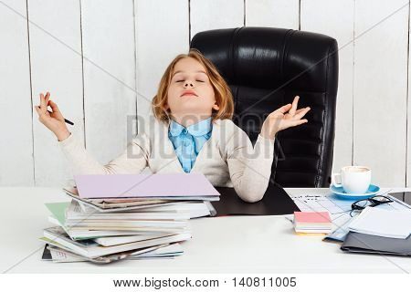 Young beautiful girl meditating at working place in office.