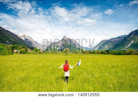 Beautiful landscape with mountains, green field and woman runninng with slovenian flag. Traveling in Triglav national park in Slovenia