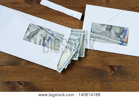 American dollars in envelopes on wooden table