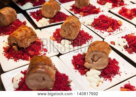 meat rolls with cous cous on white plate