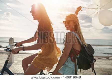 Happy Young Women On Bike Together With Balloons