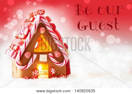Gingerbread House In Snowy Scenery As Christmas Decoration. Candlelight For Romantic Atmosphere. Red Background With Bokeh Effect. English Text Be Our Guest