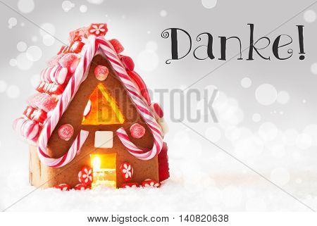 Gingerbread House In Snowy Scenery As Christmas Decoration. Candlelight For Romantic Atmosphere. Silver Background With Bokeh Effect. German Text Danke Means Thank You